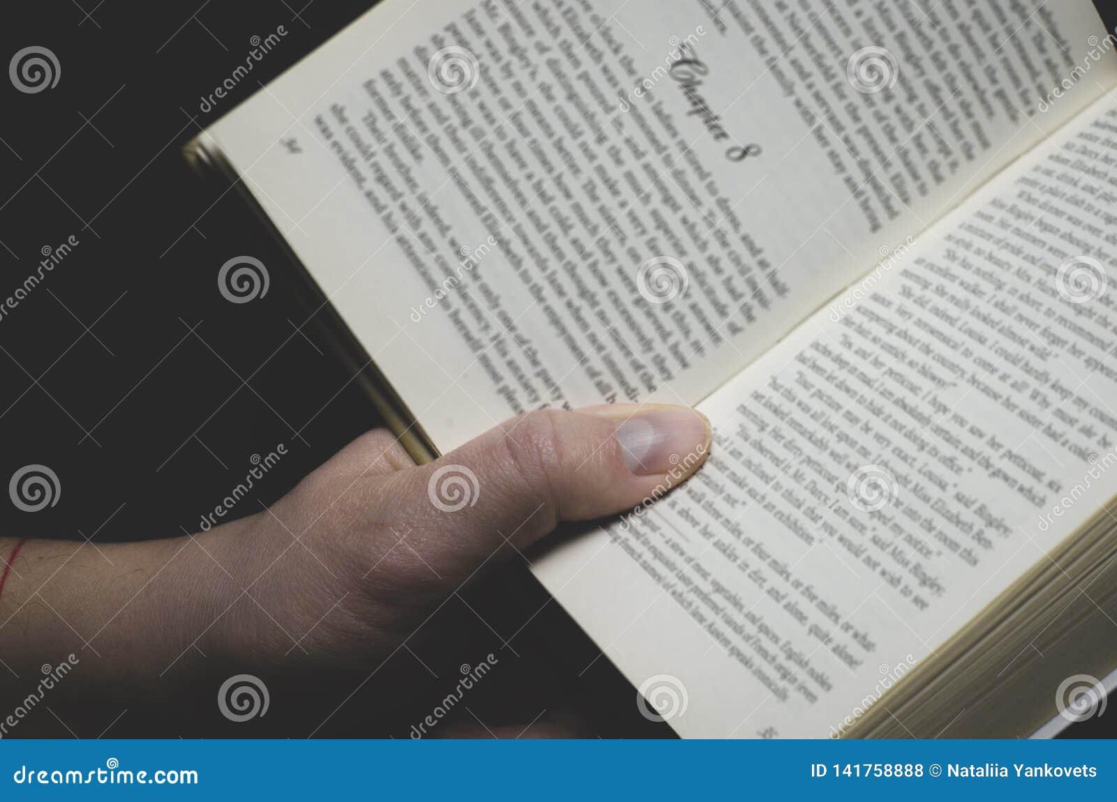 Men& x27; s de hand houdt een open boek voor lezing klaar
