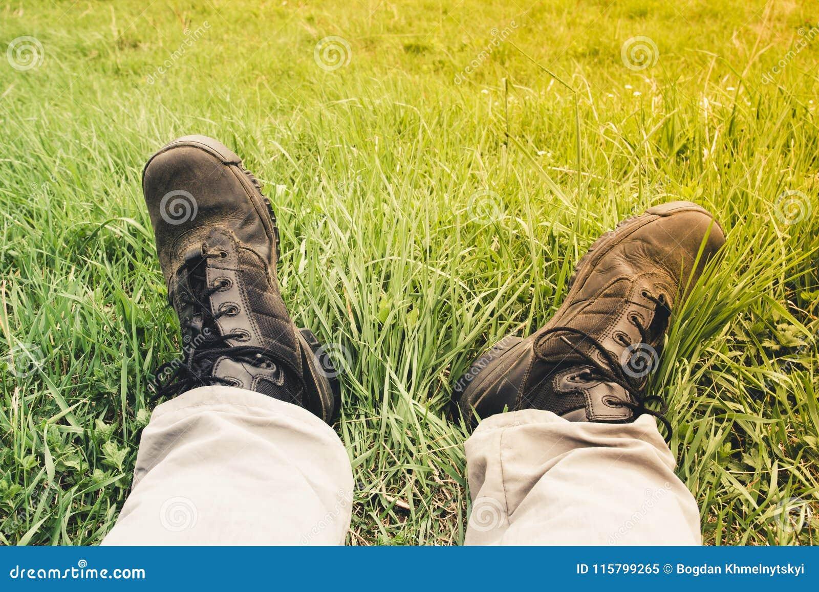Men`s feet in light Hiking pants and dirty in dust black trekkin
