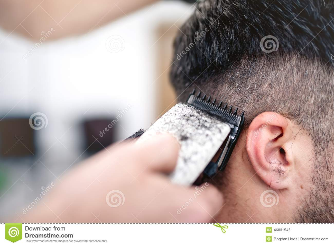 Men s hairstyling and haircutting with hair clipper in a barber