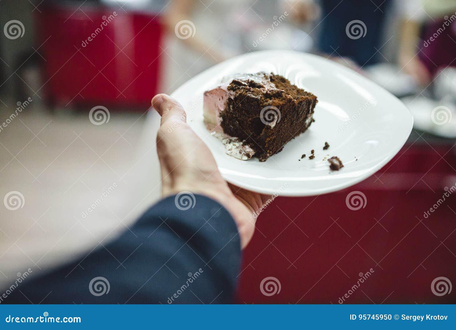 Men S Hand Holding Slice Of Glazed Chocolate Wedding Cake On The