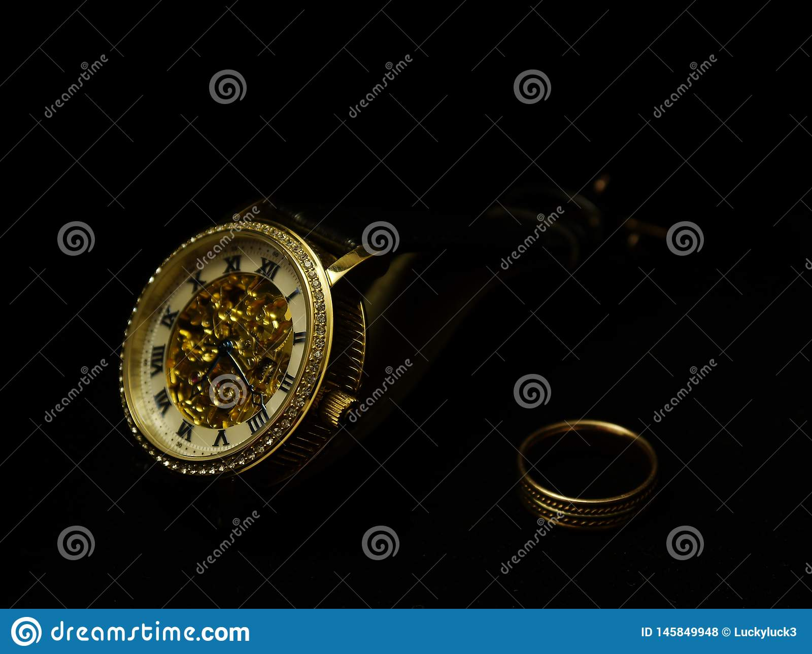 Men`s wristwatch and a ring on a black velvet.