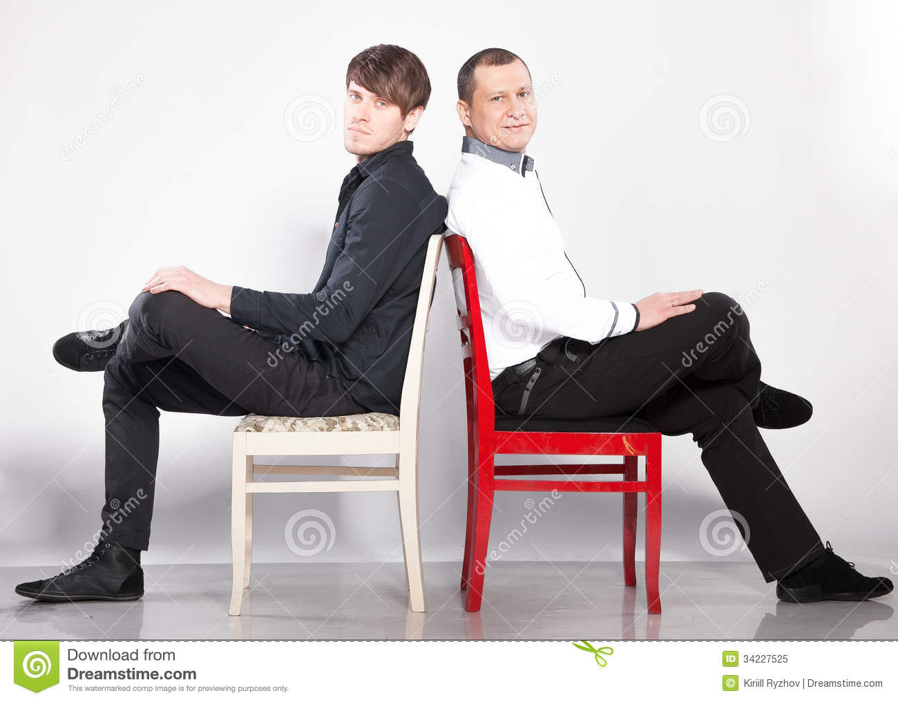 Men sitting on chairs back to back stock image image for Sitting chairs