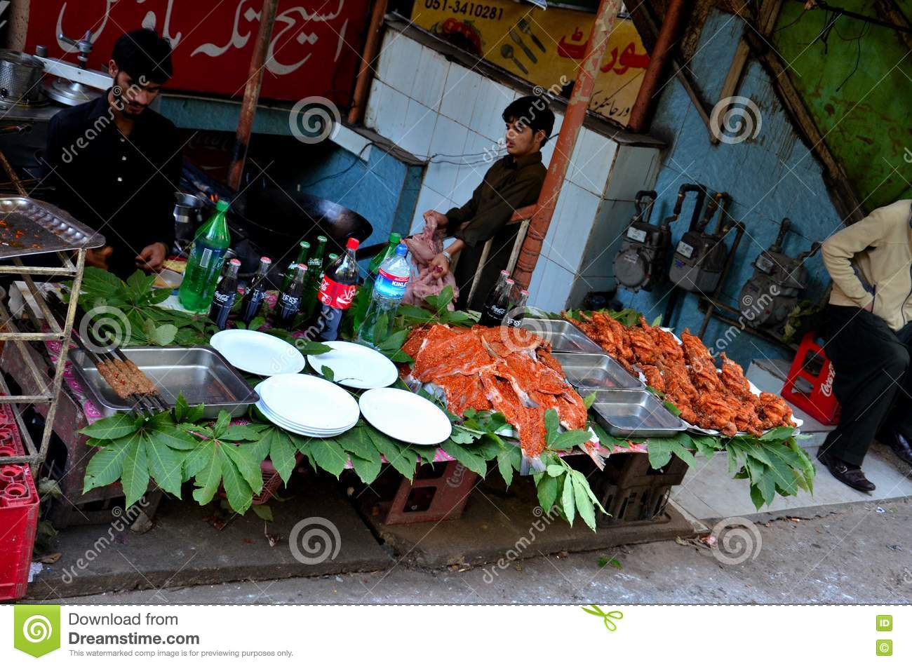Men at street side restaurant with marinated meat on display Murree Pakistan