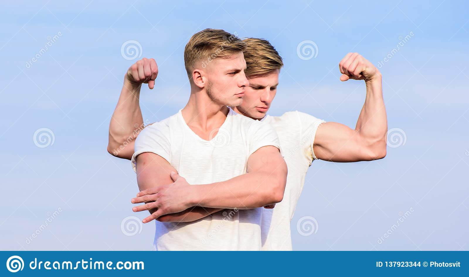 Men strong muscular athlete bodybuilder posing confidently in white shirts. Sport lifestyle and healthy body. Attractive