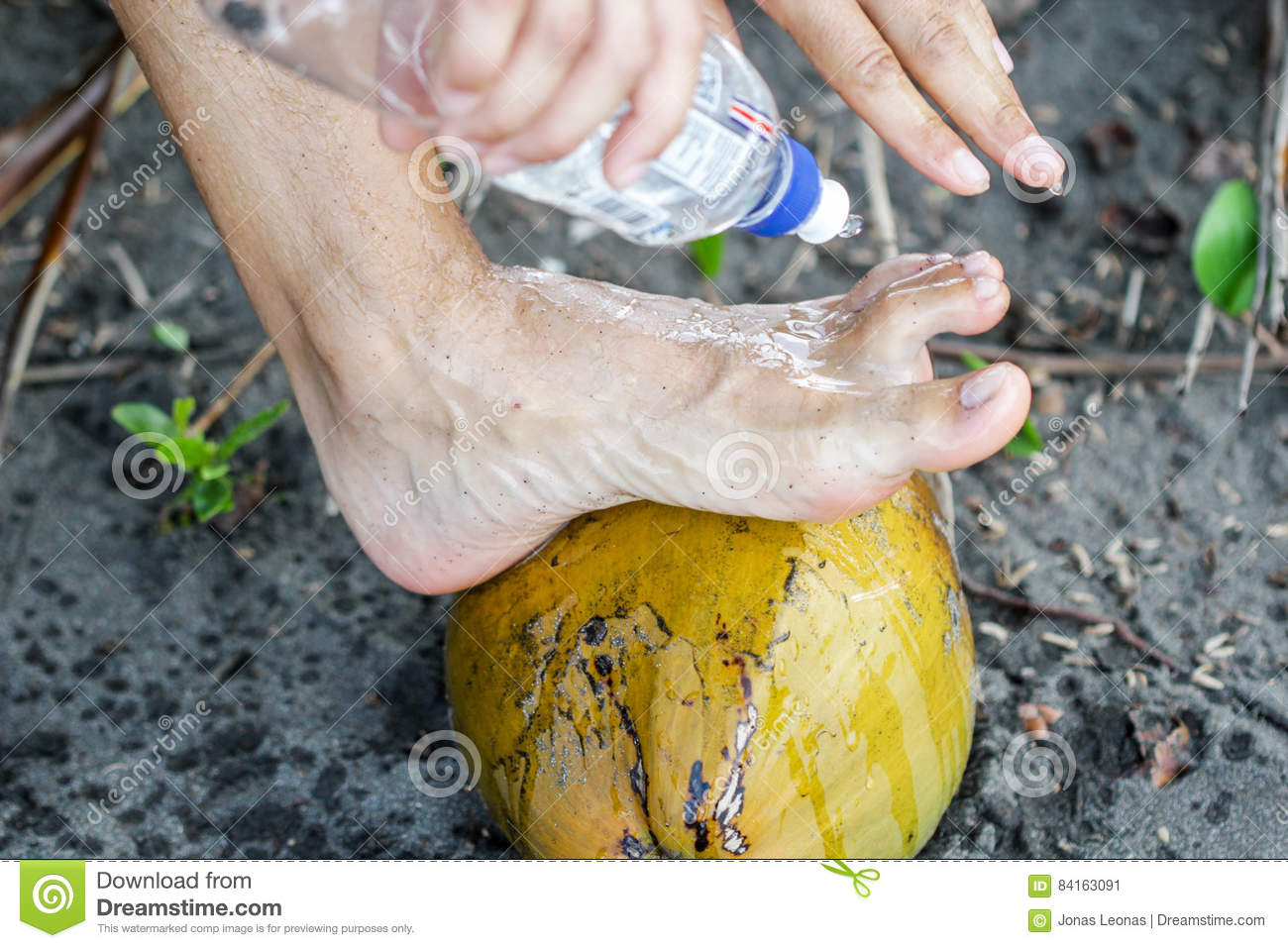Men Is Washing His Feet With His Leg On Coco Nut At The Black Sand