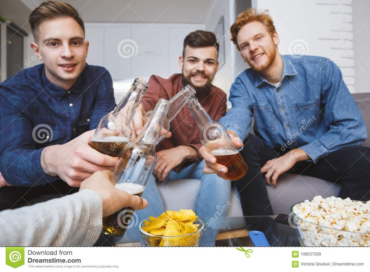 men watching sport on tv together at home cheers looking camera