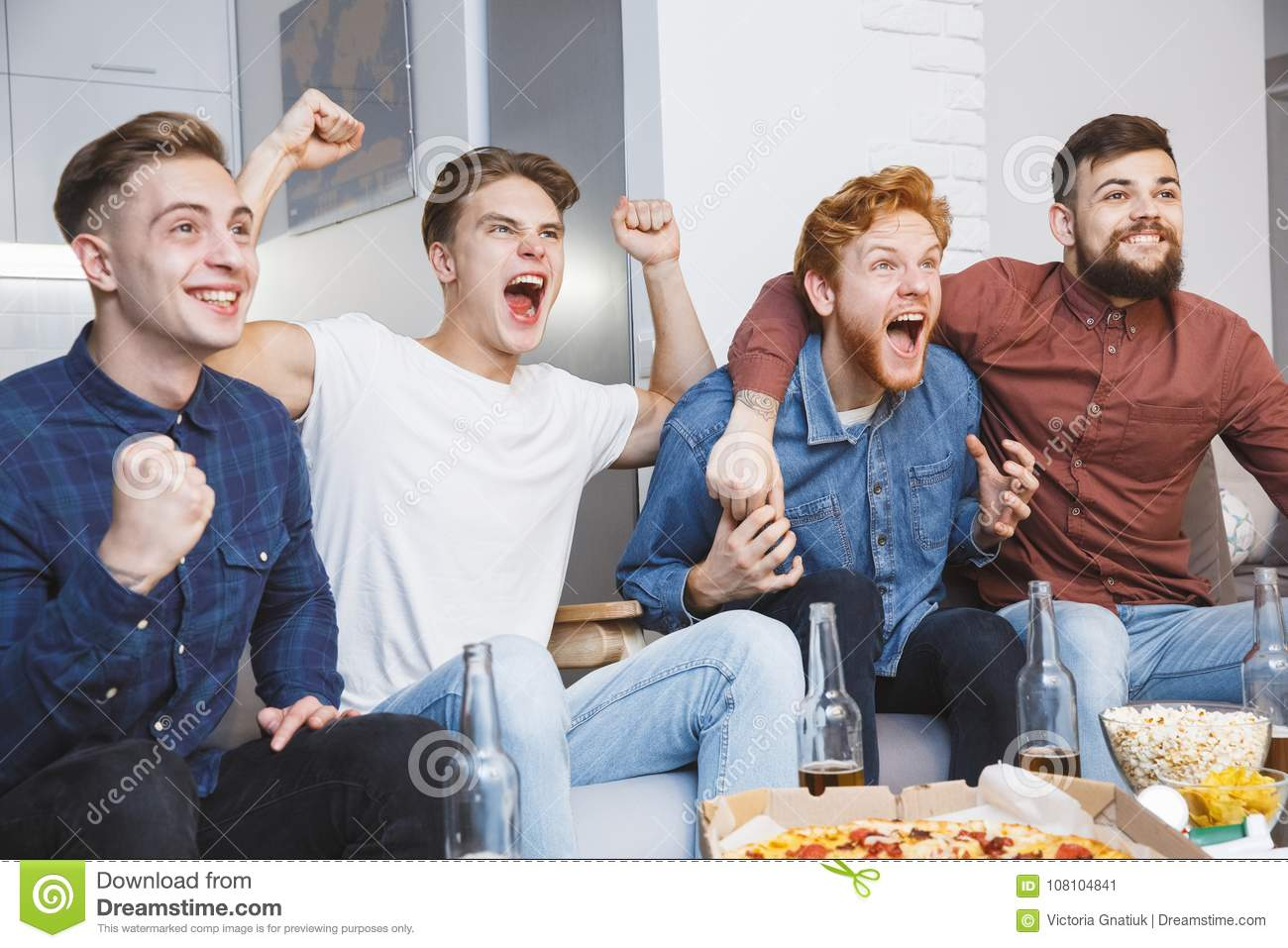 Men watching sport on tv together at home screaming cheerful