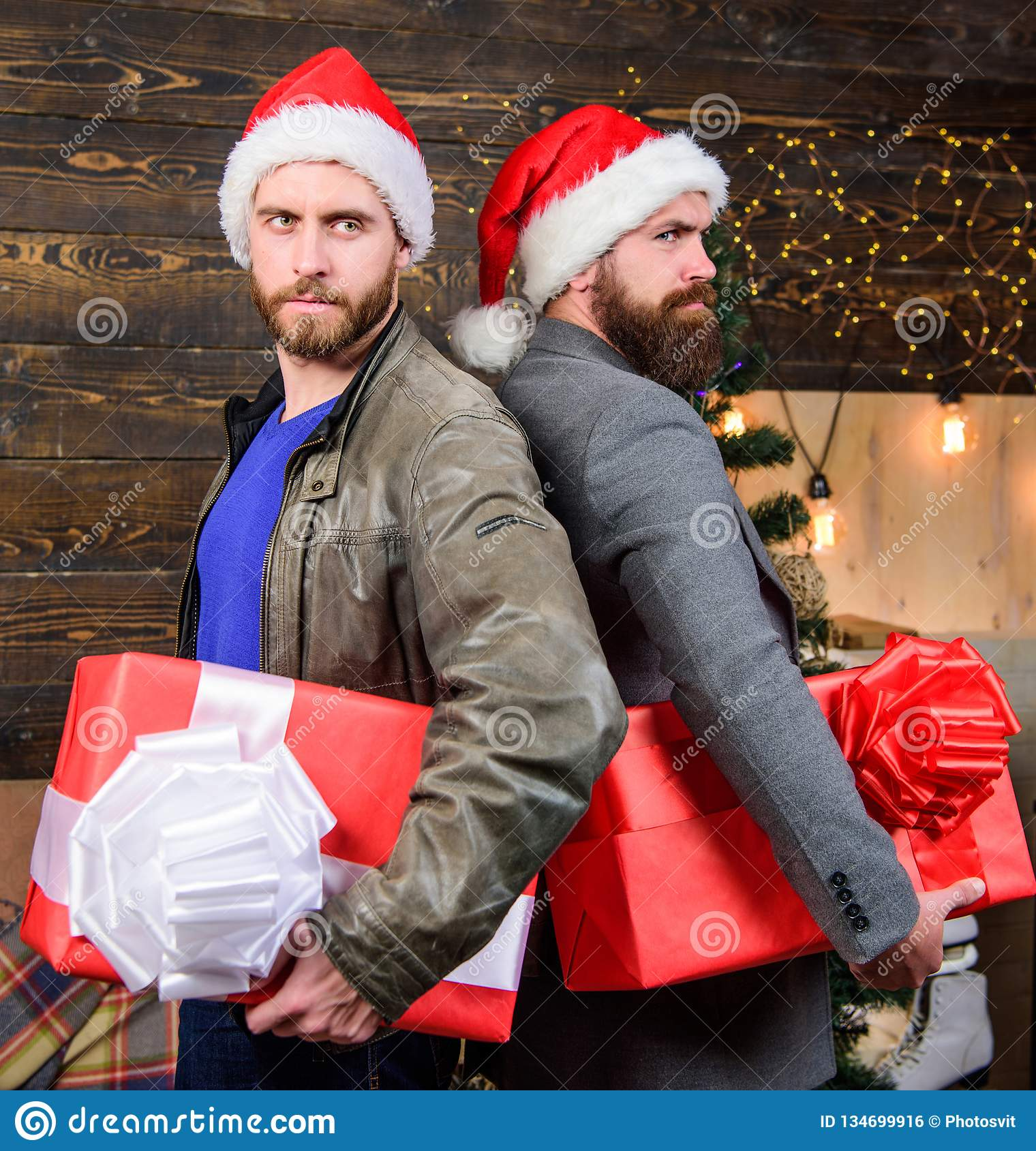 Men wear santa hat hold gift boxes. Bearded men carry present boxes. Delivery christmas present. Christmas is coming