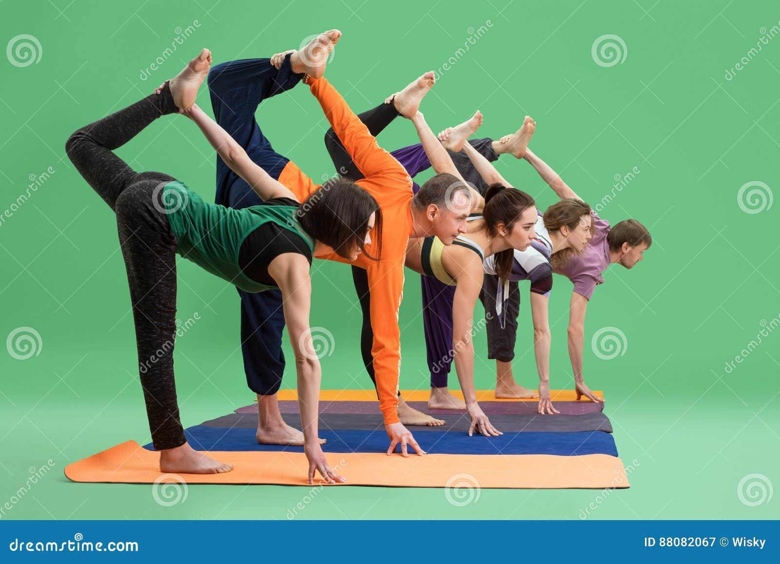 Men and women do yoga in studio green background