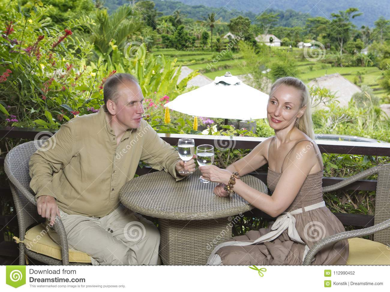 The man and the woman with glasses sit on a balcony overlooking rice terraces and mountains