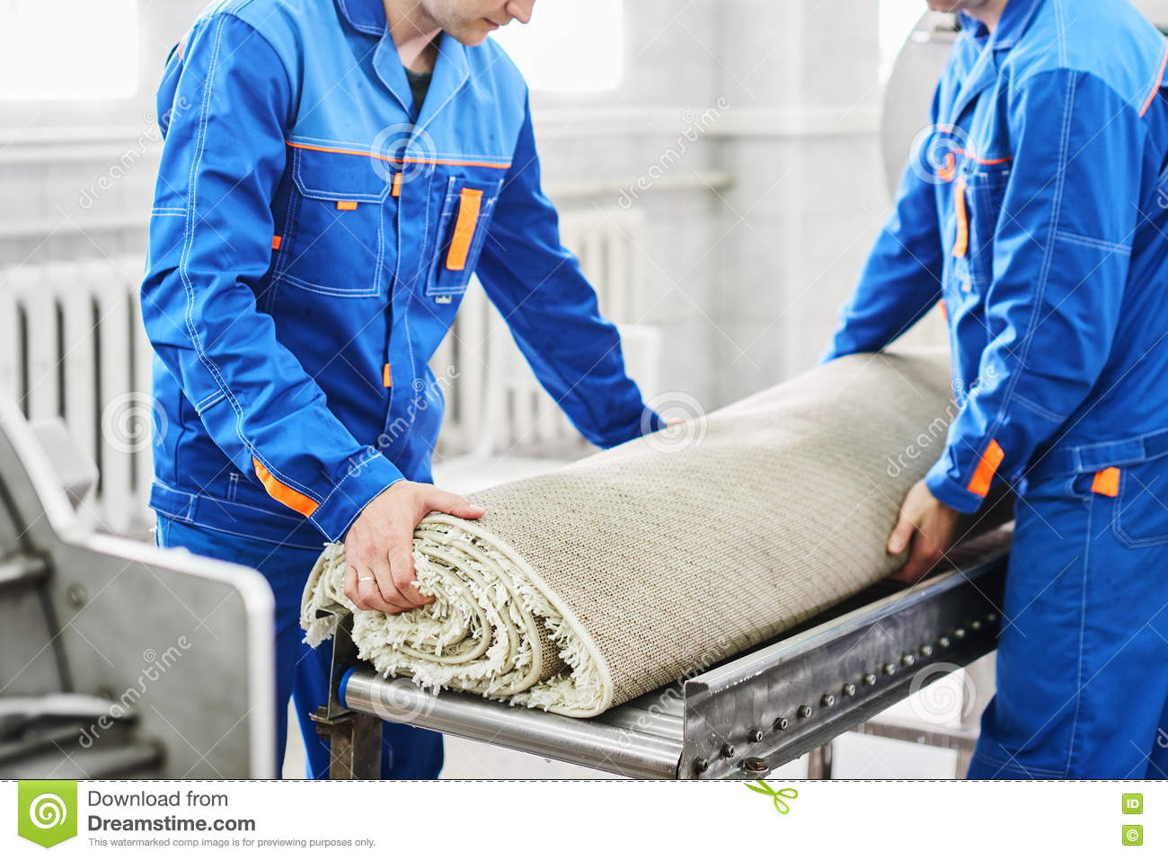 Men workers cleaning get carpet from an automatic washing machine and carry it in the clothes dryer