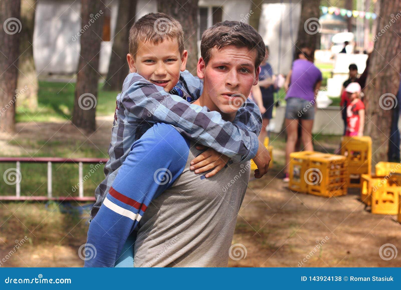 Mena, Ucr?nia - 11 de maio de 2018: O indiv?duo dos esportes est? retendo um menino pequeno no seu Jogos ao ar livre lazer