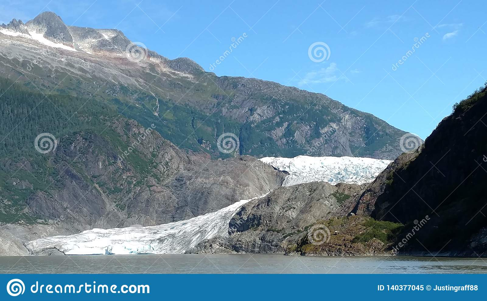 Mendenhall Glacier in Juneau Alaska. Large Glacier sliding into a lake with a waterfall beside it. Very popular tourist stop