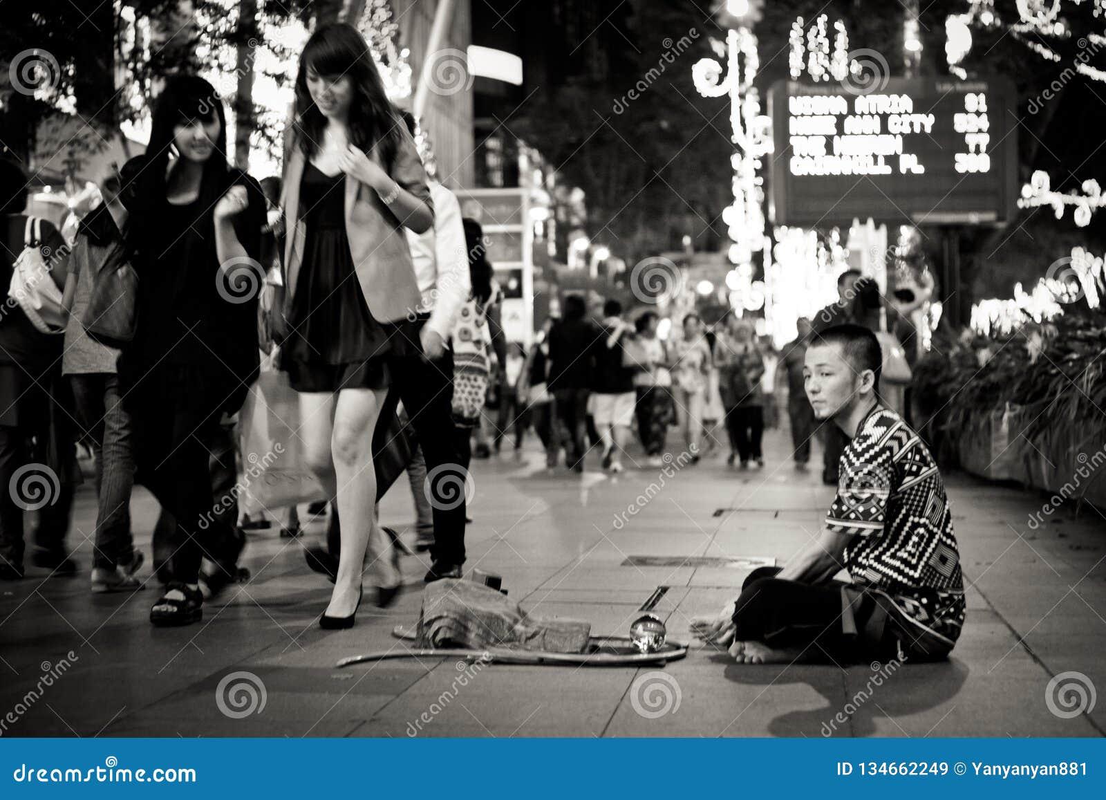 Mendigo e mulher rica em um distrito de compra em Singapura