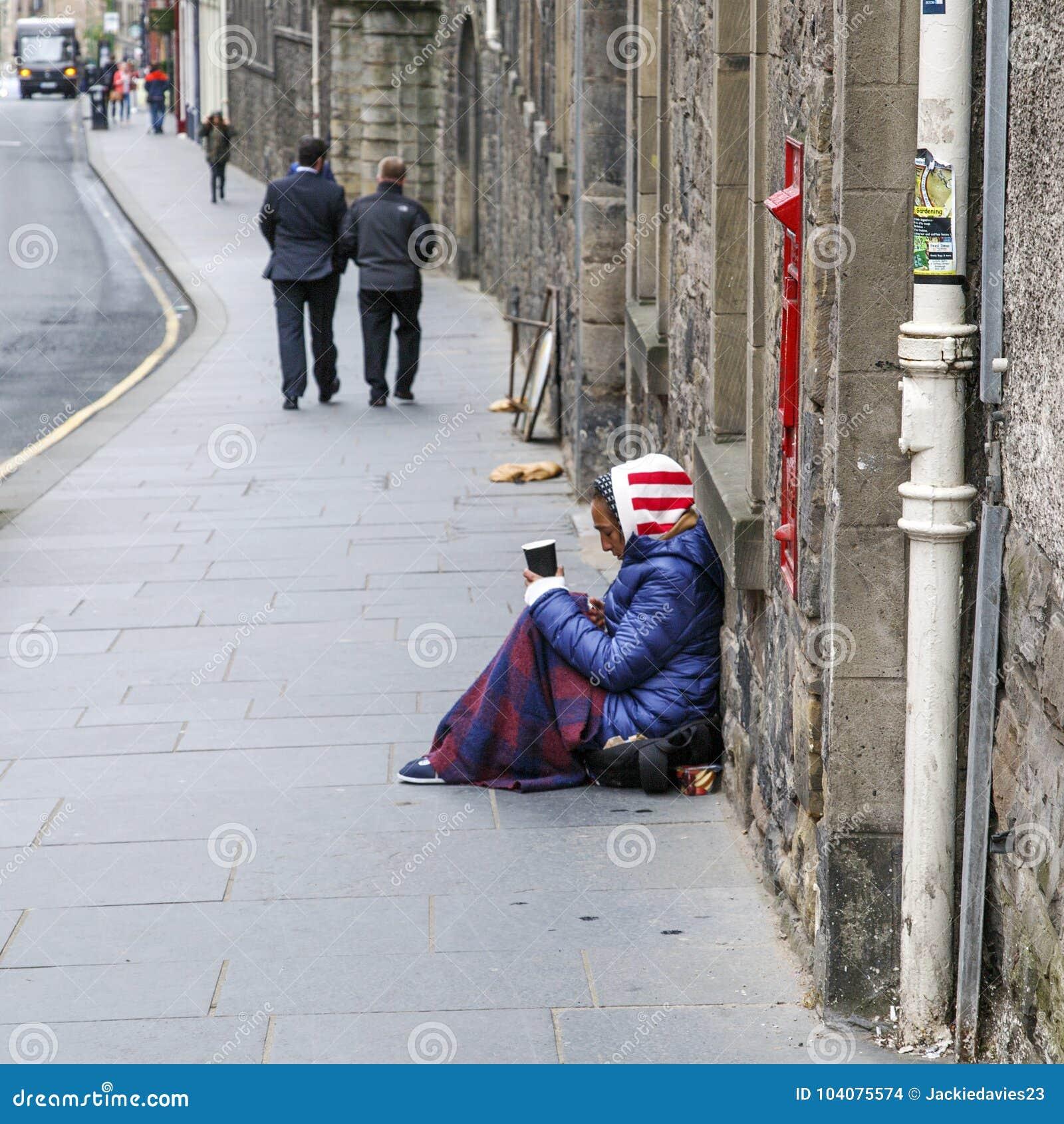 Mendigo fêmea que senta-se no pavimento que guarda um copo