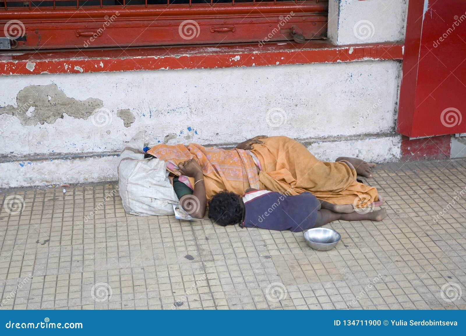 Mendigos sin hogar madre y niño que duermen en el camino