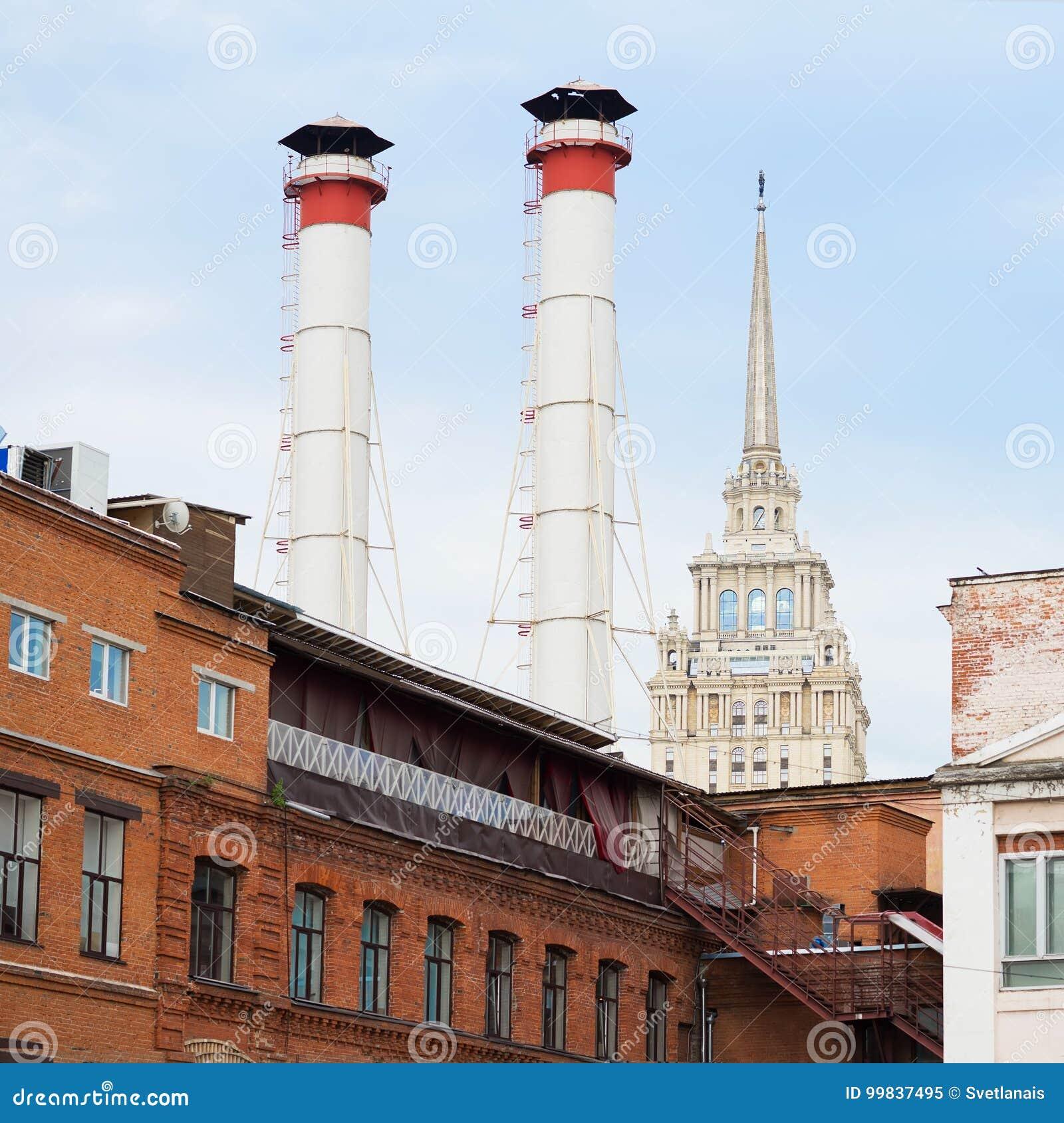 Mengeling van twee pijpen en gebouwen van verschillende tijden tegen hemel De oude Industriële bouw van fabriek van rode baksteen