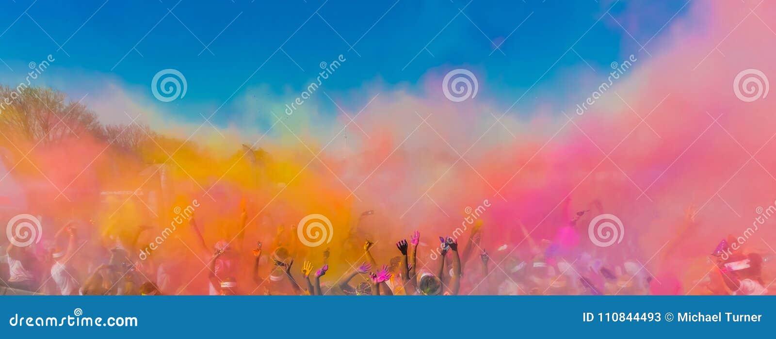 Menigte die heldere gekleurde poederverf in de lucht werpen, Holi Fes