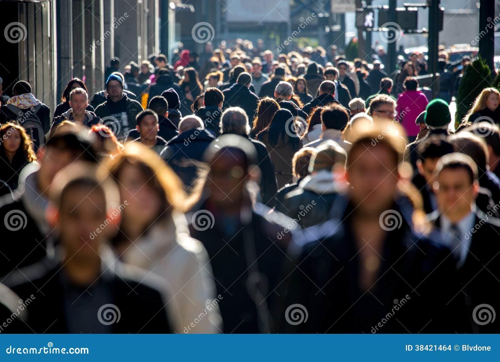 Menigte van mensen die op straatstoep lopen