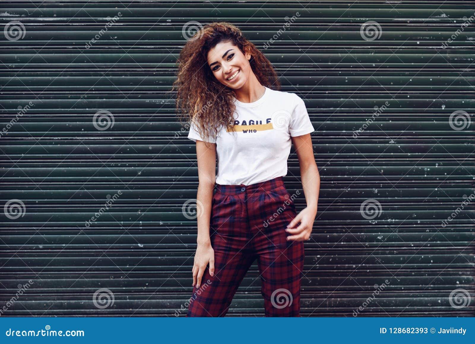 Menina árabe de sorriso na roupa ocasional na rua