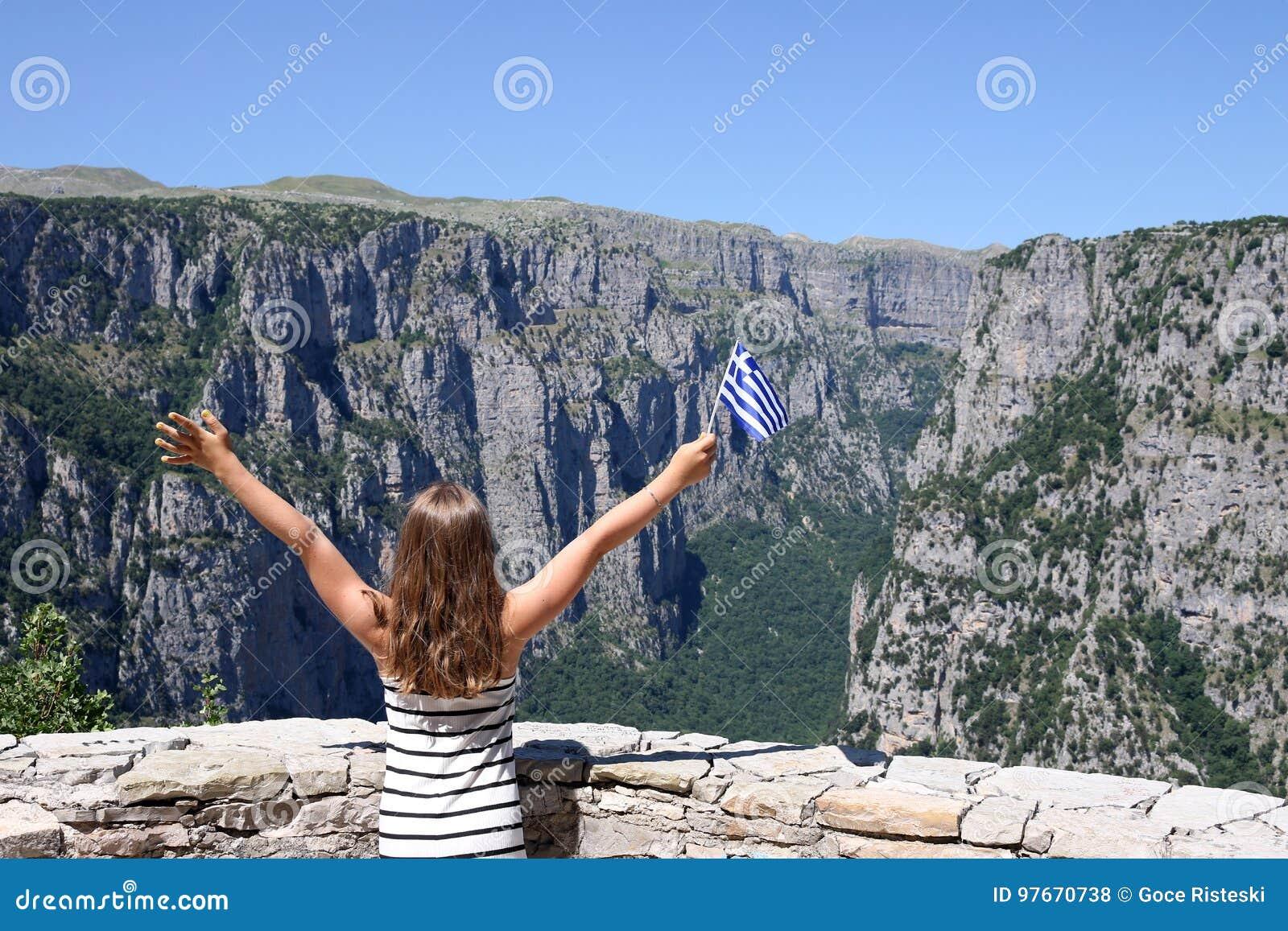 A menina acena com uma bandeira grega no desfiladeiro Zagoria de Vikos