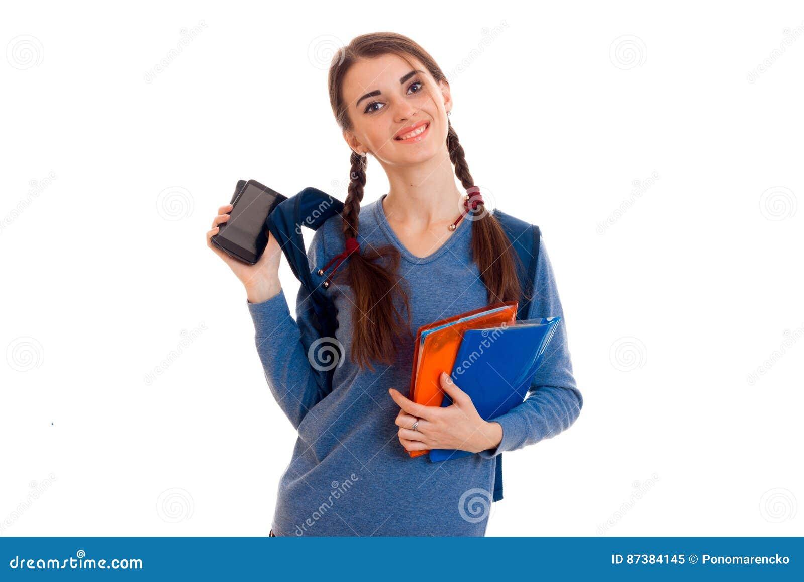 A menina adolescente alegre olha na câmera e guarda dobradores com cadernos