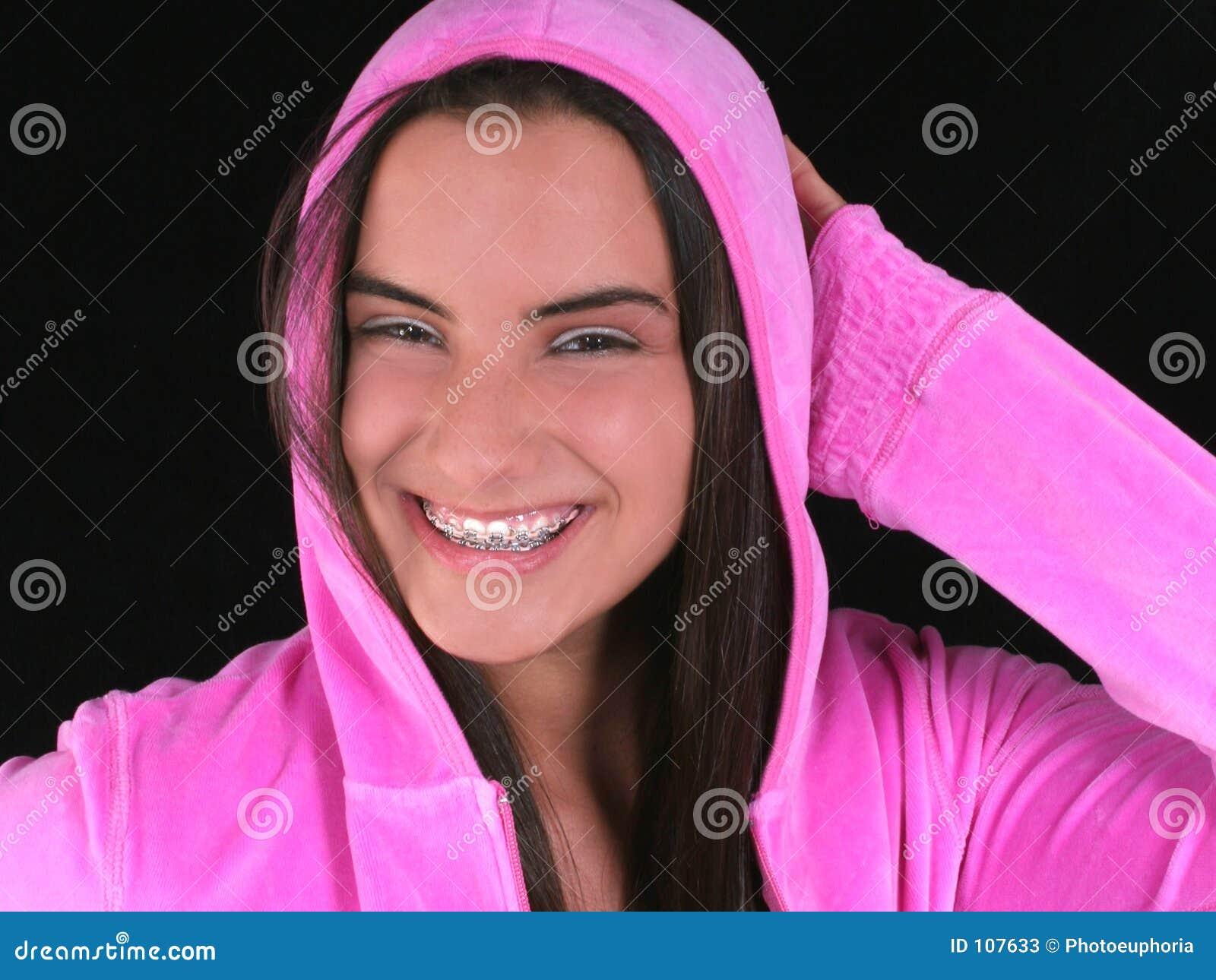 Menina adolescente bonita com as cintas no revestimento encapuçado cor-de-rosa