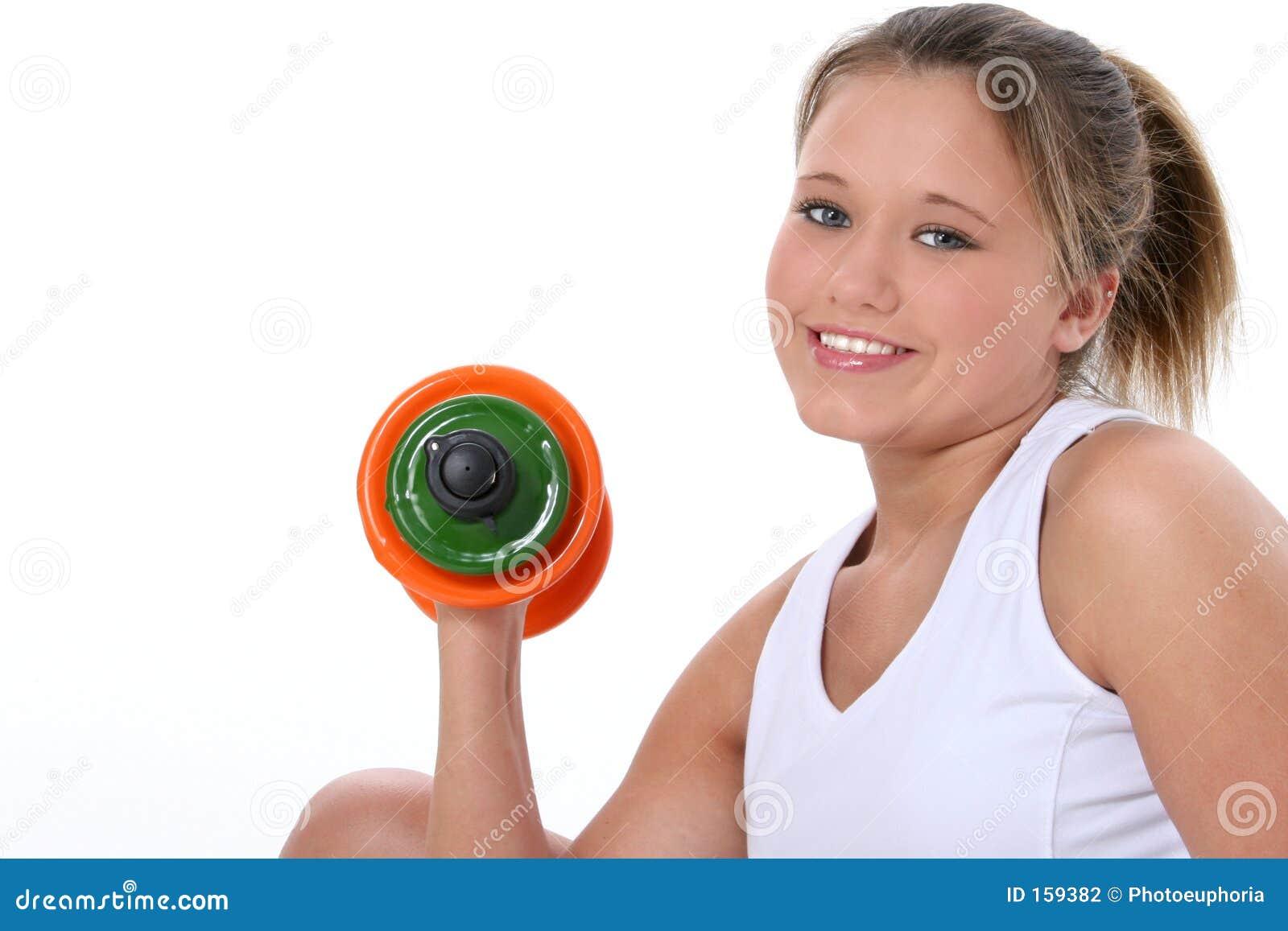 Menina adolescente bonita na roupa do exercício com pesos da mão