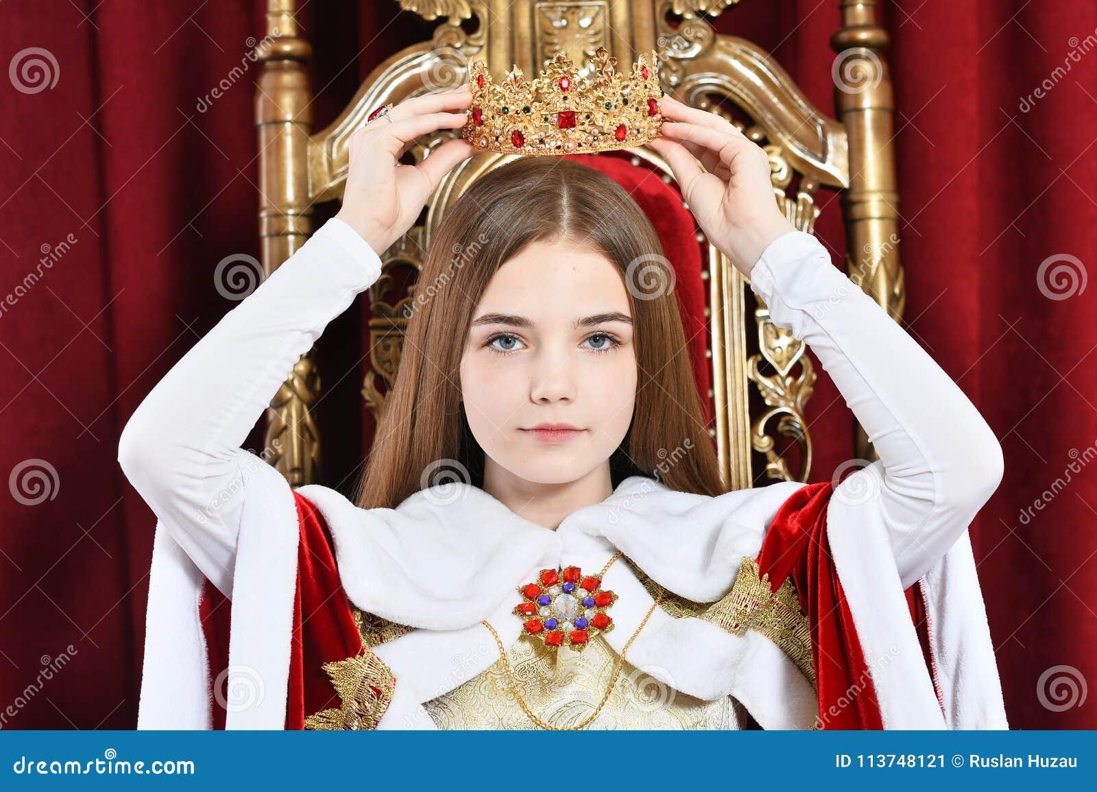 Menina adolescente bonita que guarda a coroa que senta-se na poltrona do vintage