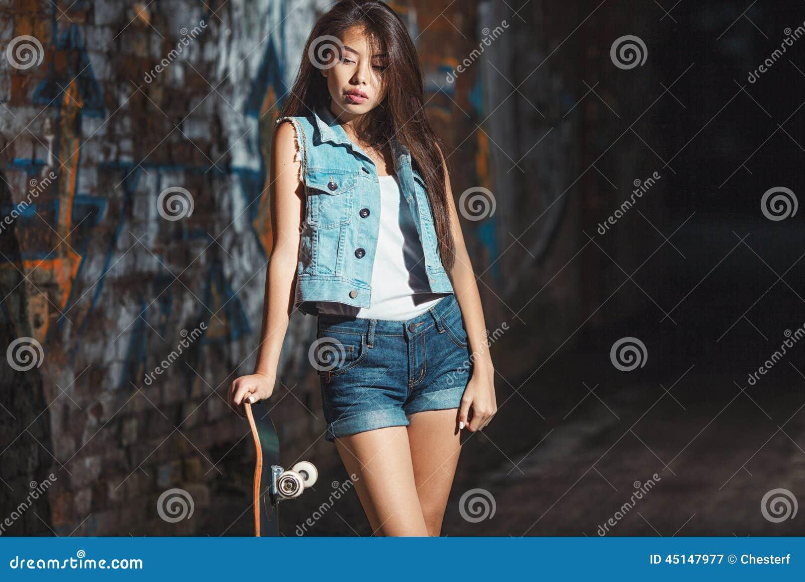 Menina adolescente com placa do patim, estilo de vida urbano