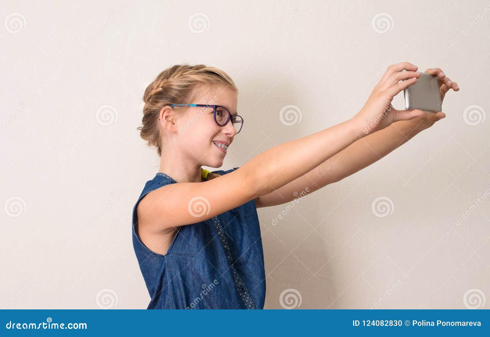 Menina adolescente consideravelmente de sorriso nos vidros que fazem a foto do selfie em esperto