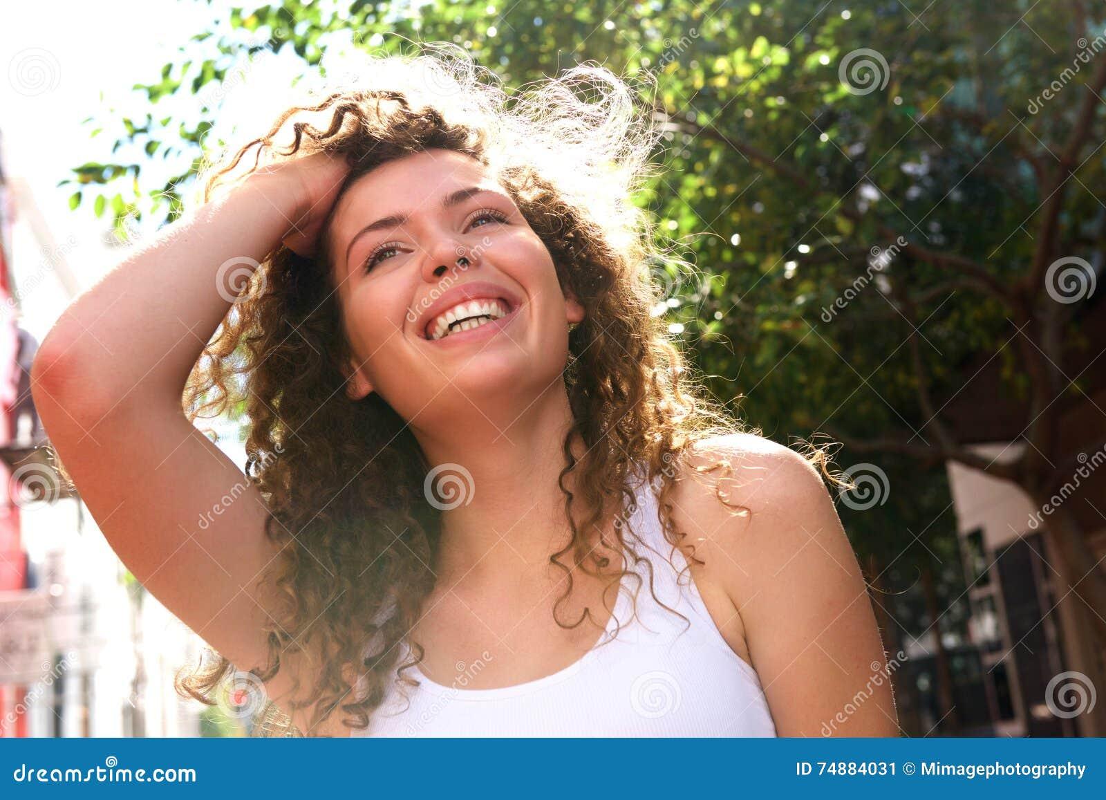 Menina adolescente de sorriso com mão na parte externa ereta do cabelo