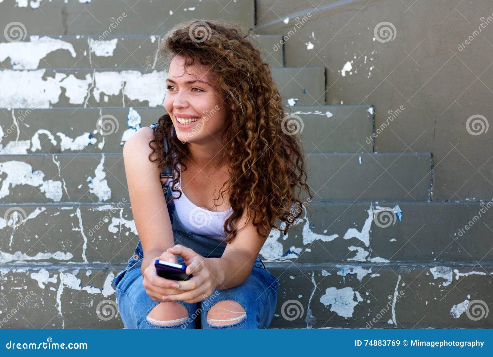 Menina adolescente de sorriso que guarda o telefone e que senta-se em etapas