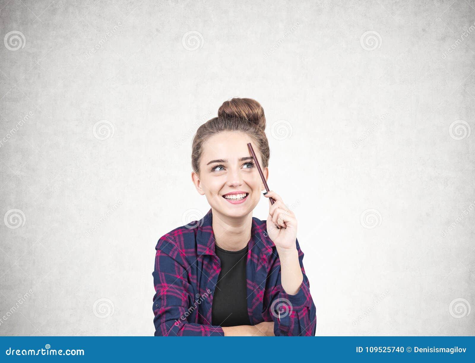 Menina adolescente de sorriso que pensa, lápis, concreto