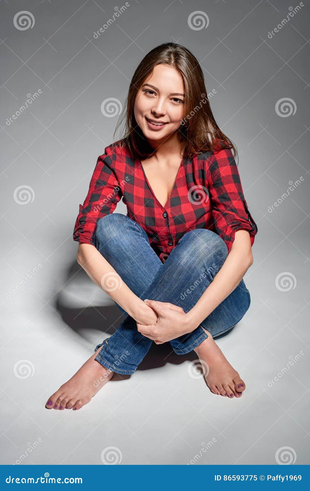 Menina adolescente de sorriso que senta-se com os pés descalços no assoalho que sorri na câmera