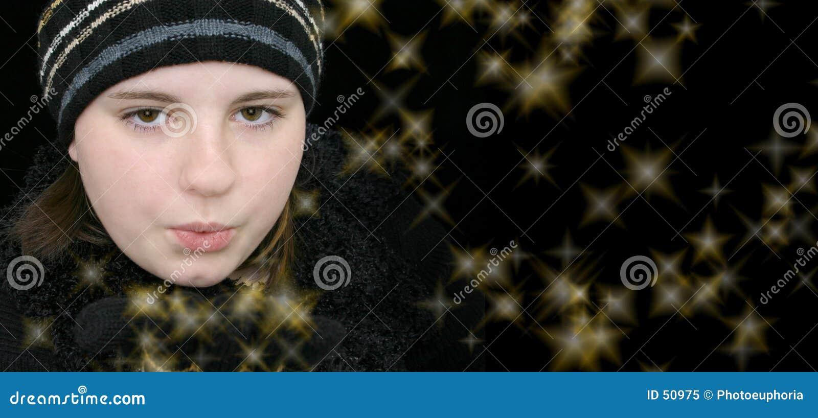 Menina adolescente do inverno que funde estrelas mágicas
