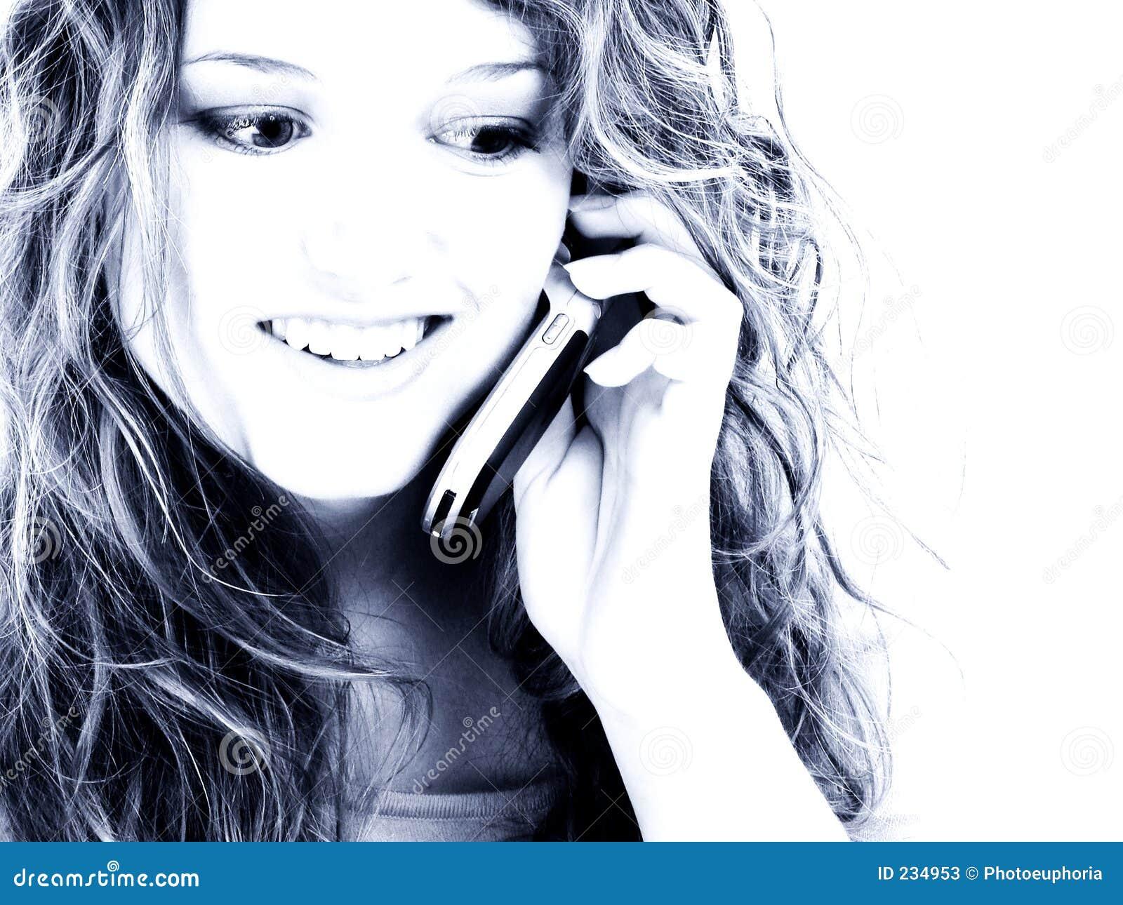 Menina adolescente dos anos de idade dezesseis bonitos no telemóvel