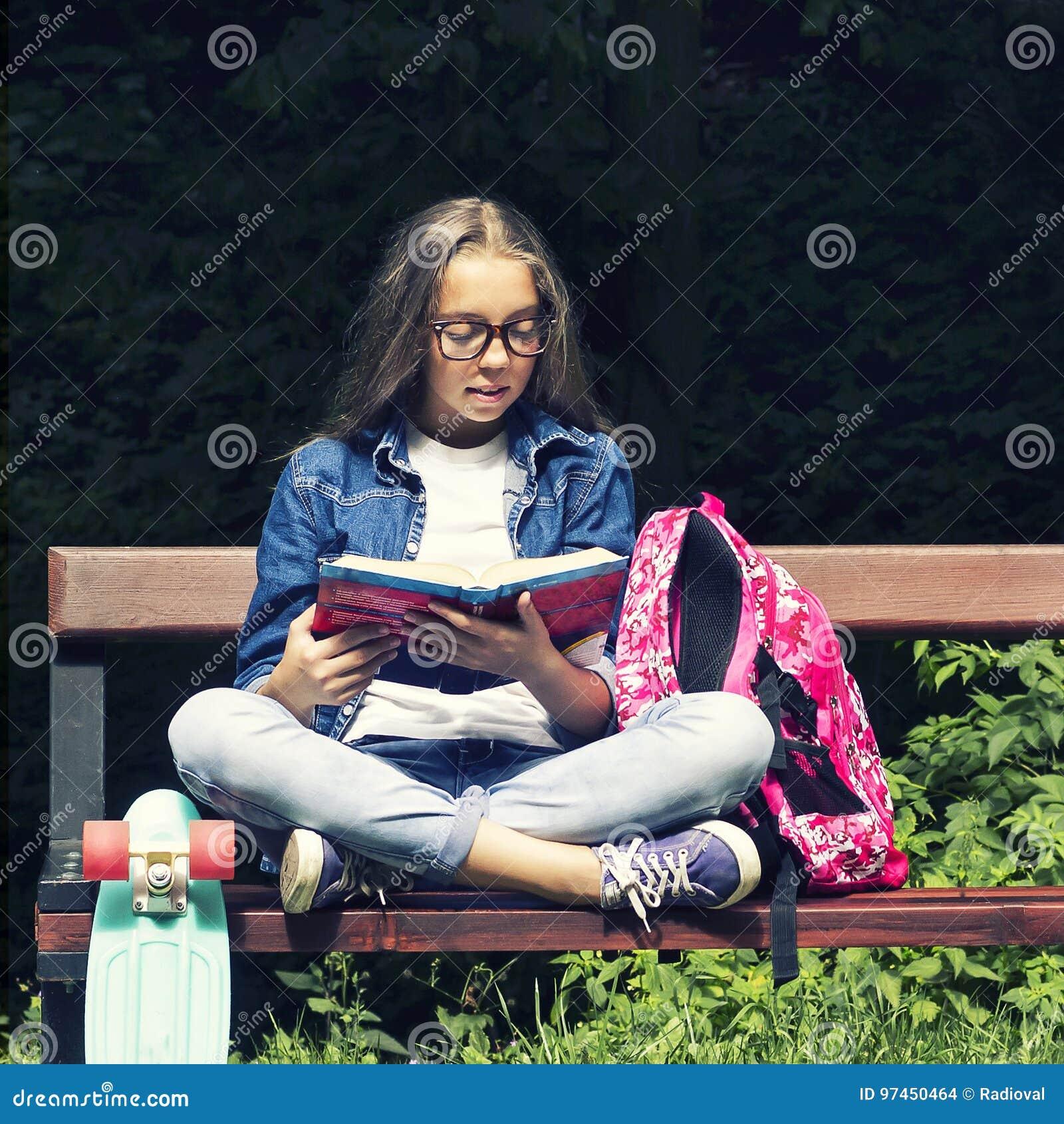 Menina adolescente loura bonita na camisa das calças de brim que lê um livro no banco com uma trouxa e um skate no parque