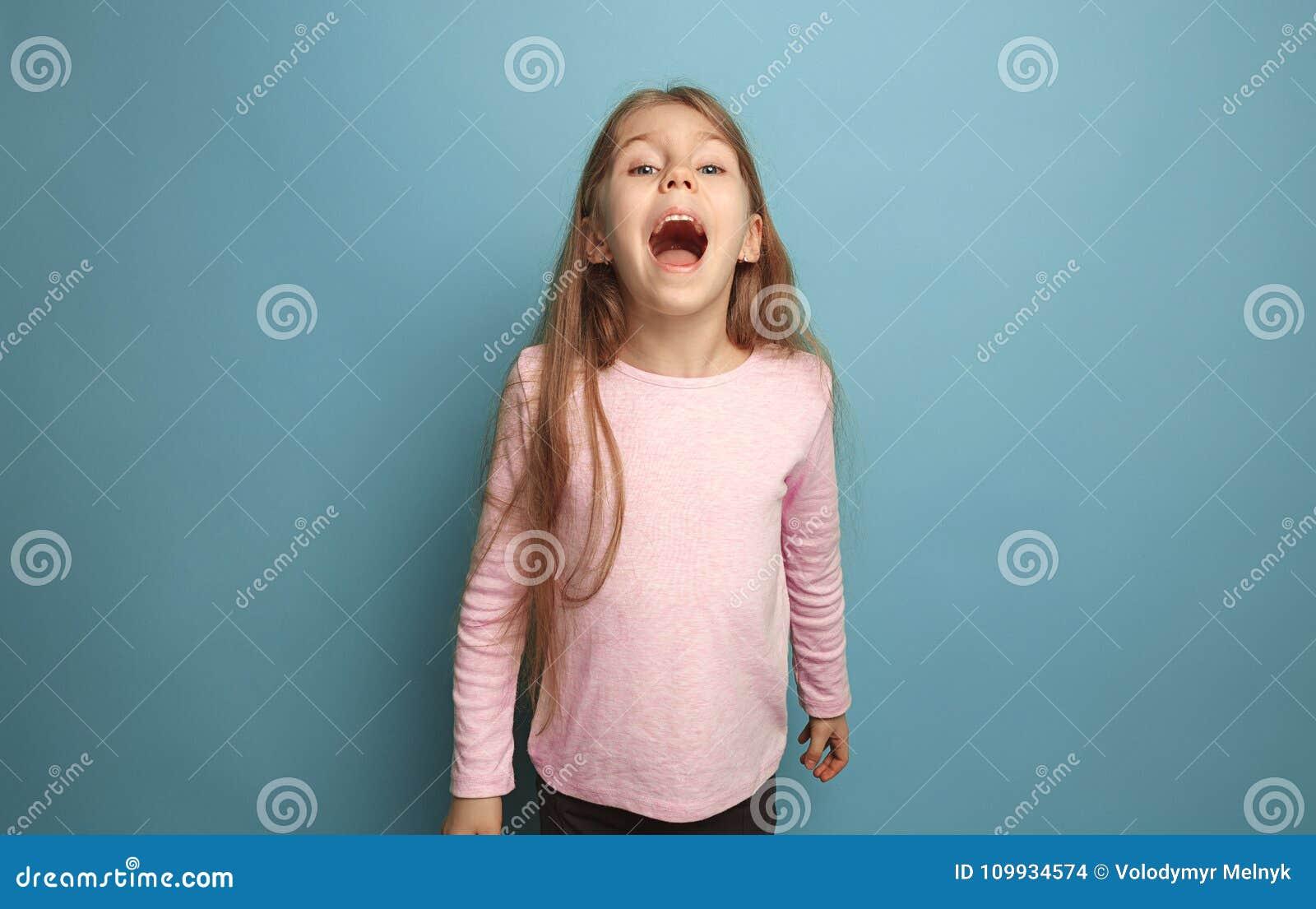A menina adolescente loura emocional tem um olhar da felicidade e gritar Tiro do estúdio