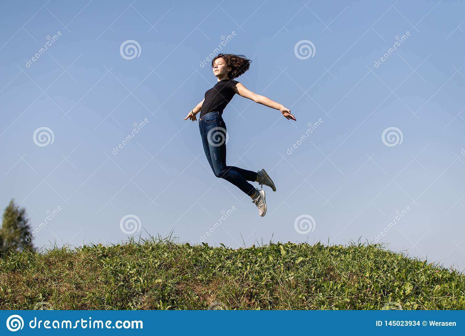 Menina adolescente magro vestida nas calças de brim e um salto preto da parte superior alto sobre a grama verde contra o céu