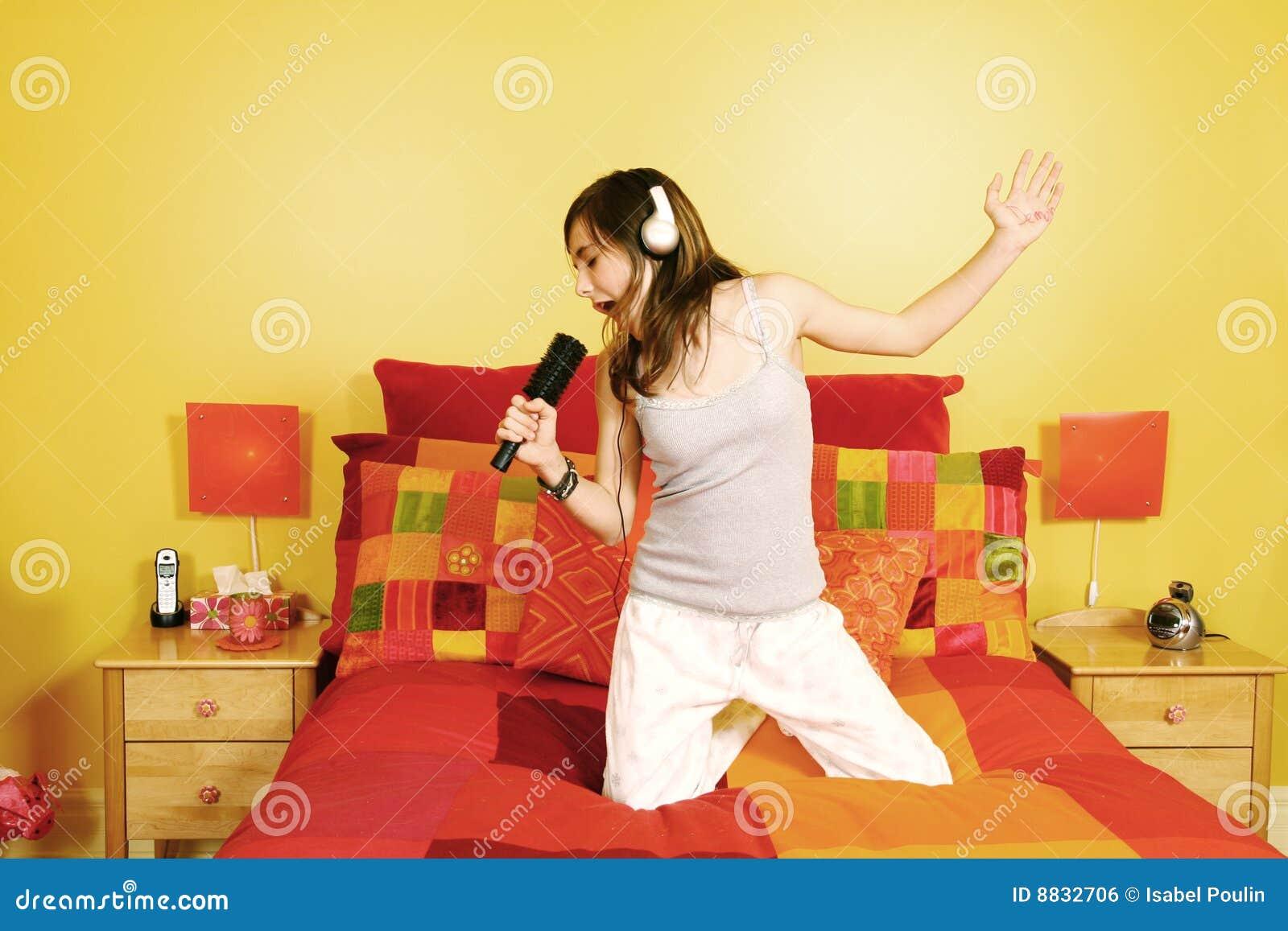 Menina adolescente que canta no quarto