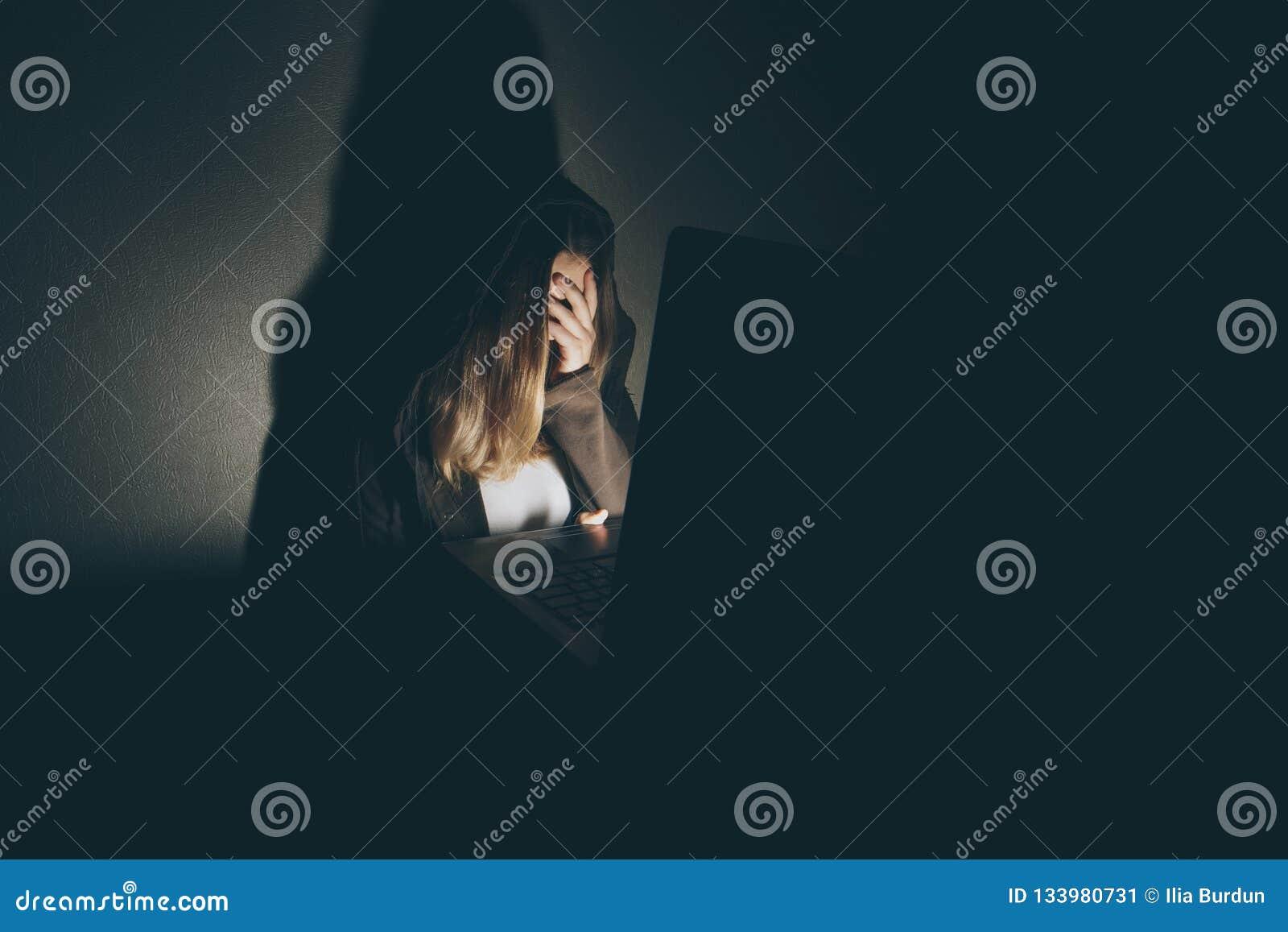 Menina adolescente que senta-se excessivamente no portátil do computador em casa é uma vítima de redes tiranizando em linha do so