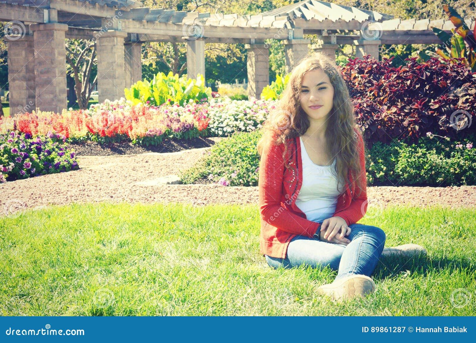 Menina adolescente que senta-se na grama com flores de florescência