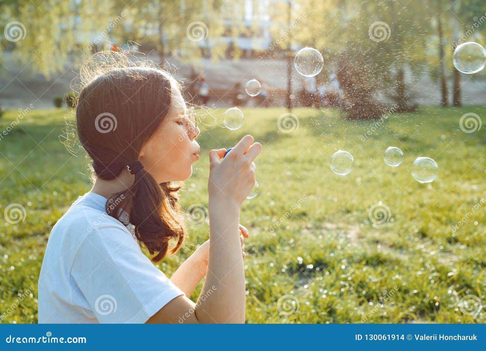 Menina adolescente que tem o divertimento no parque - bolhas de sabão de sopro, hora dourada