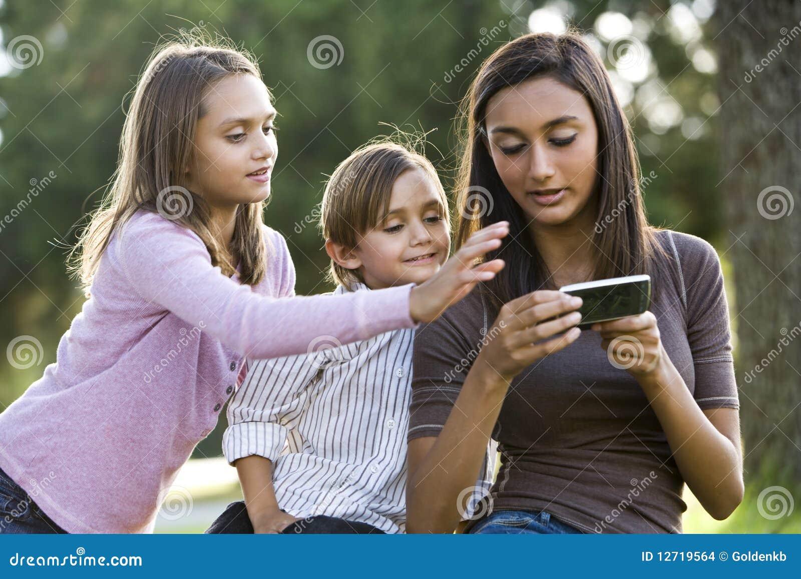 Menina adolescente que texting, relógio mais novo dos irmãos