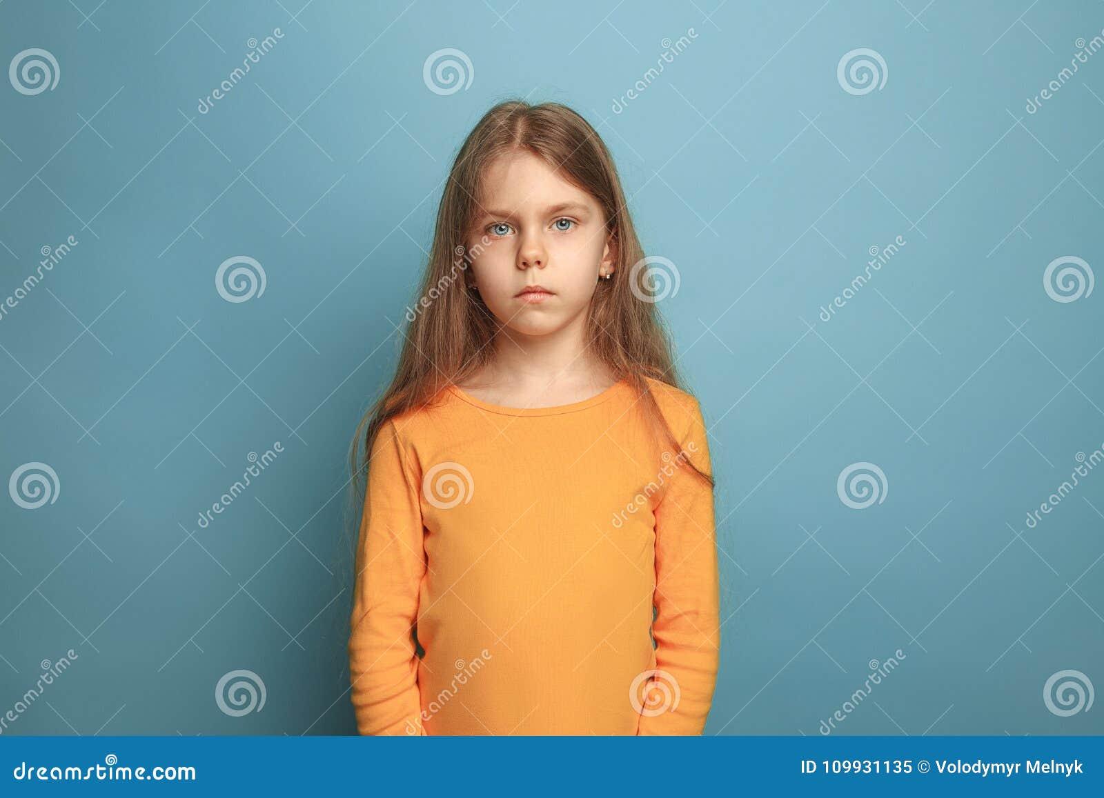 A menina adolescente séria em um fundo azul Expressões faciais e conceito das emoções dos povos