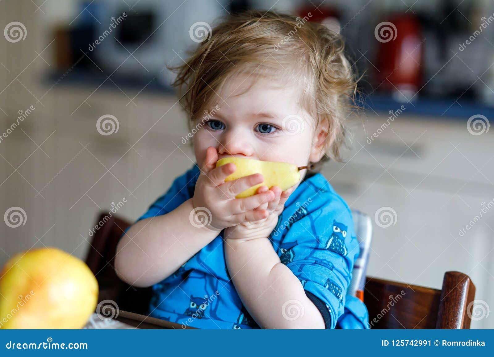 Menina adorável bonito da criança que come a pera fresca Criança feliz com fome do bebê de um ano que guarda o fruto Menina em do
