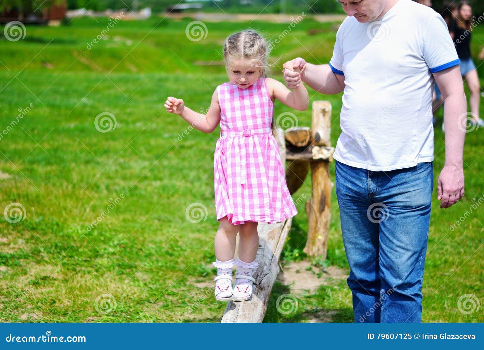 Menina adorável com o pai que guarda sua mão que anda na madeira no dia de verão ensolarado