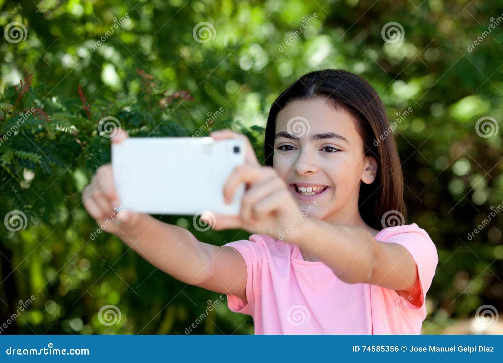 Menina adorável do preteen com móbil