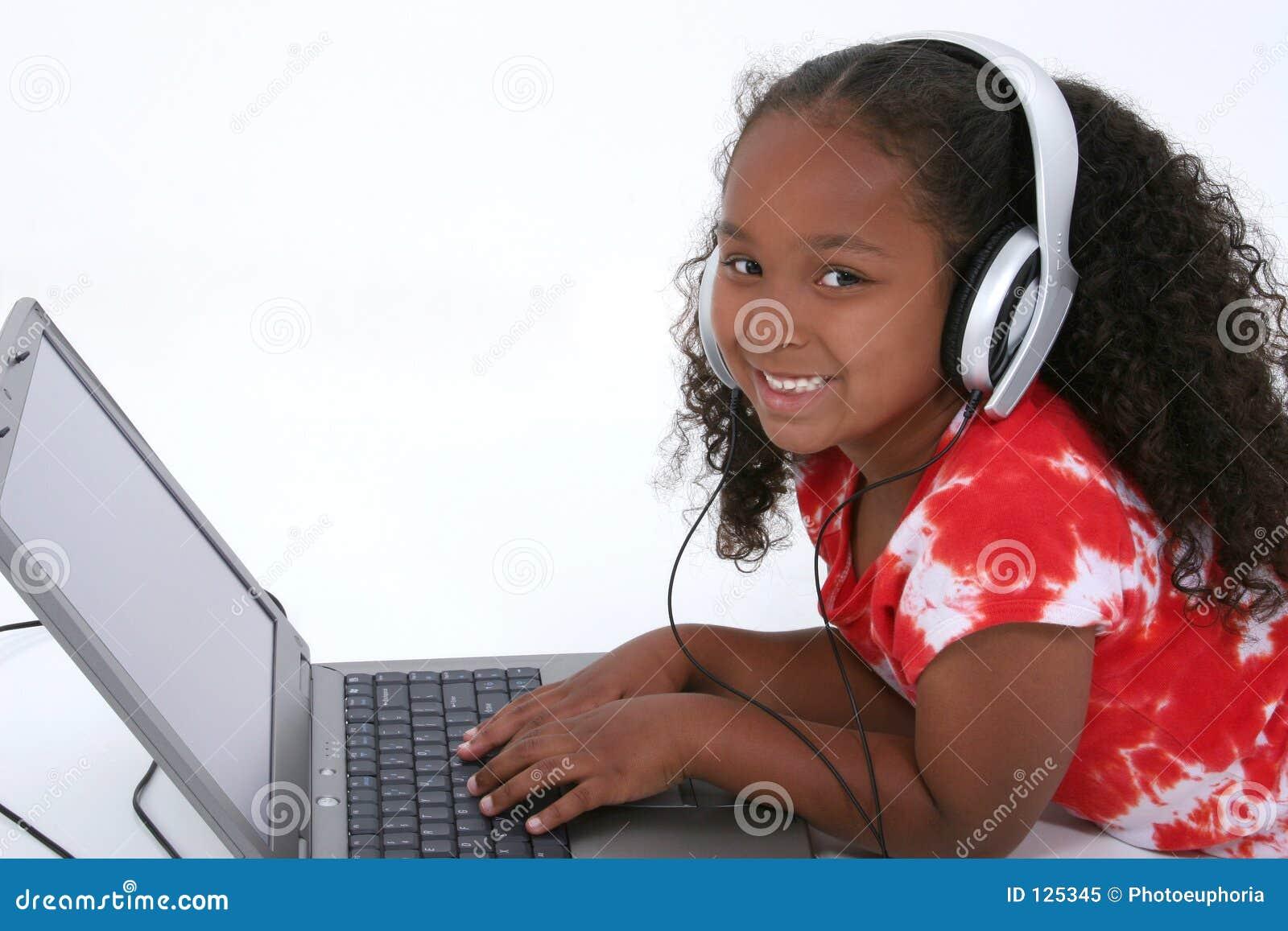 Menina adorável dos anos de idade seis que senta-se no assoalho com computador portátil
